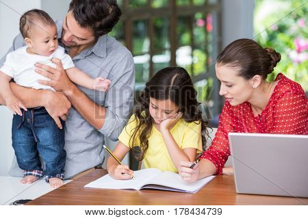 Mother helping daughter with homework while father standing at desk