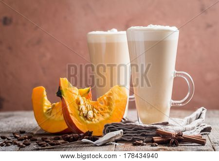 Pumpkin latte with whipped cream and spices on wooden background