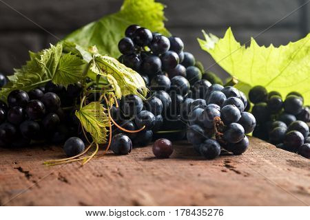 Grapes with leaves on vintage wooden table, close-up.