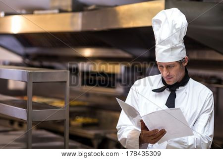Handsome chef reading menu in a commercial kitchen