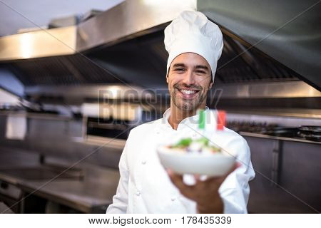 Handsome chef presenting meal with italian flag in a commercial kitchen
