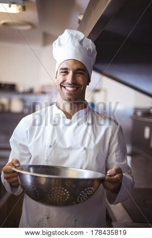 Handsome chef holding colander in a commercial kitchen