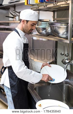 Handsome employee doing dishes in commercial kitchen