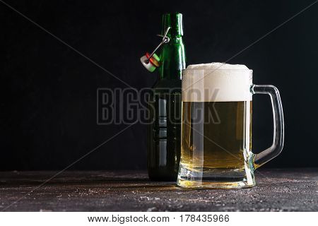 Glass mug of light beer and bottle on dark background