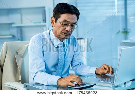 Focused asian businessman using calculator and laptop in office