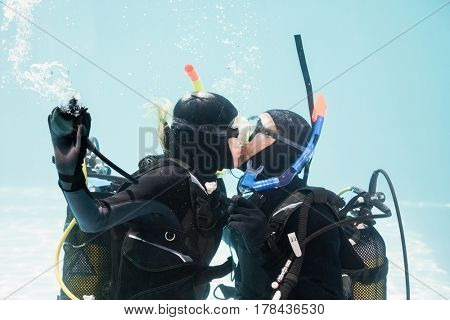 Couple kissing underwater while scuba diving in swimming pool
