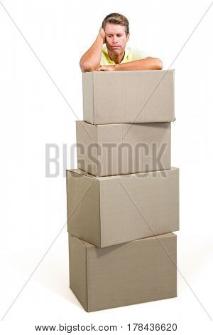 Thoughtful man standing with boxes against white background