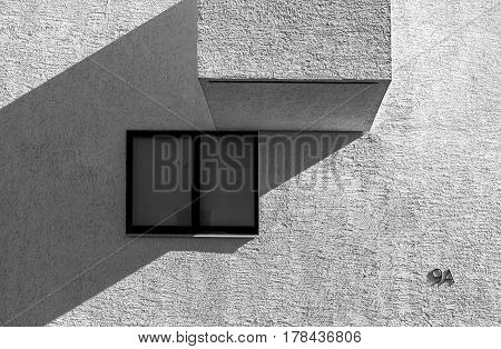 High contrast black and white picture of modern abstract looking building with window and balcony detail
