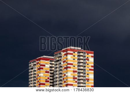 Two colorful residential buildings against stormy dark blue sky. Abstract looking high contrast picture with copy space on the top