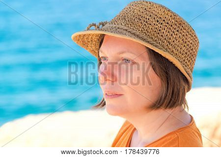Relaxed beautiful adult caucasian woman with straw hat enjoying sunny afternoon female head portrait by the sea in summer holiday vacation resort