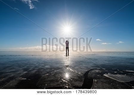 a man standing on frozen lake with sun and flare effects at winter