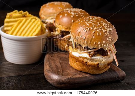 Homemade Mini Beef Burgers with Coleslaw Salad on Little Wooden Cutting Board. Barbecue Meat Sandwiches on Rustic Table.