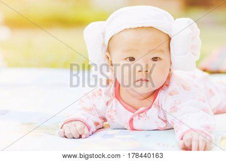 Cute  Baby Lie Prone On Ground At Park