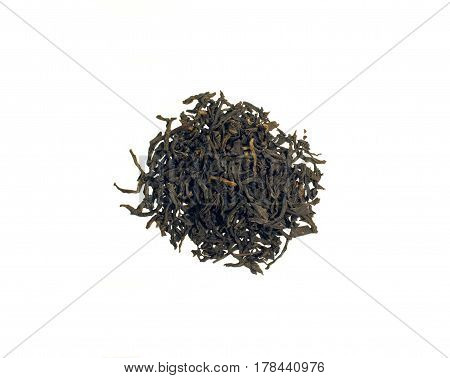 Still Life with a pile of black Assam tea leaves scattered on a table isolated on white background