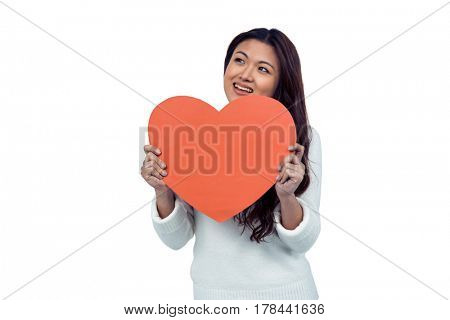 Smiling Asian woman holding paper heart on white screen