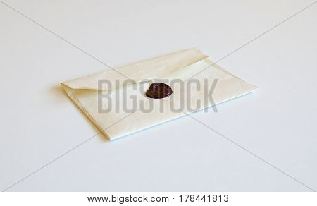 view of white envelope from handmade paper with a stamp of sealing wax isolated on white background