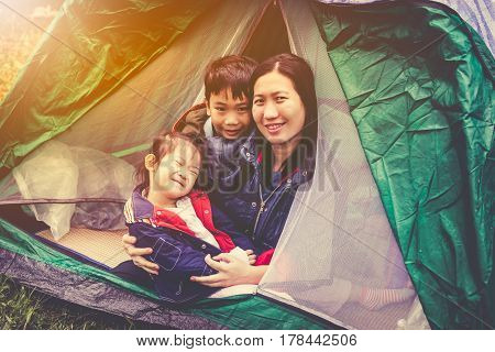 Vintage tone photo of happy asian family looking at camera on camping trip in their tent outdoors on summer morning with bright sunlight. Mother with son and daughter smiling happy together.