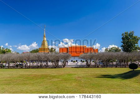 Bright sky with grass field in Nan Museum in front of golden pagoda in Wat Phra That Chang Kham Nan ProvinceThailand