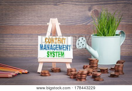 Content Management System Business Concept. Miniature watering pot with fresh green spring grass and small change.