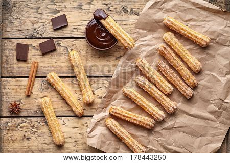 Churros traditional Spanish breakfast homemade sweet dough dessert pastry street fast food snack with chocolate on vintage wooden table background flat lay