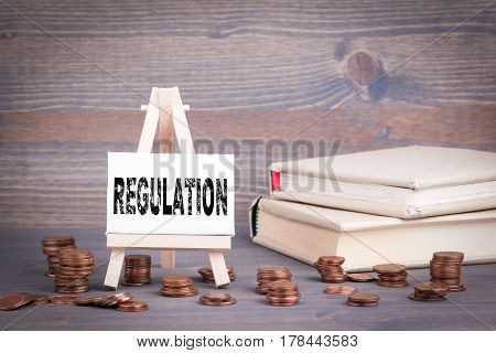 Regulation Business Concept. Miniature easel with small change.