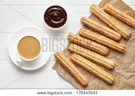 Churros traditional Spain street fast food baked sweet dough snack with chocolate and coffee, rustic decorative parchment paper, white table background. Flat lay top view