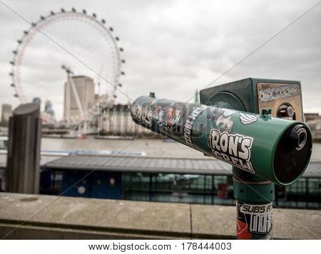 LONDON UK - 8 MARCH 2017: A stickered tourist telescope on the banks of the River Thames pointing towards the London Eye in the background blur.