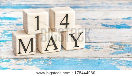May 14th. Wooden cubes with date of 14 May on old blue wooden background.