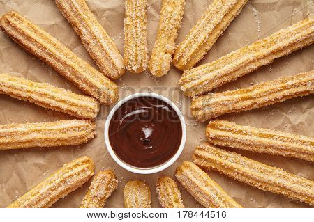 Churros traditional Spain breakfast or lunch street fast food baked sweet dough snack dessert with chocolate on rustic decorative parchment paper background. Flat lay top view