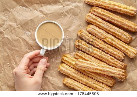 Churros traditional homemade Spain breakfast or lunch meal street fast food baked sweet dough snack dessert with coffee on rustic decorative parchment paper background. Flat lay top view