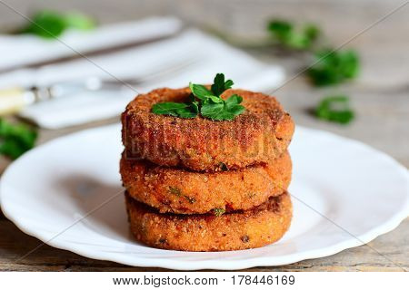 Homemade carrot cutlets on a plate. Delicious fried carrot cutlets with green onions and parsley. Healthy meatless cutlets recipe. Closeup