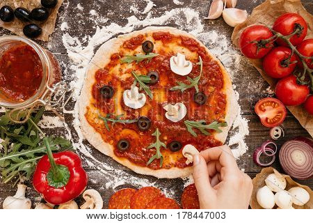 Cooking Pizza. Hands Adding Ingredients To Pizza. Pizza Ingerdients On The Wooden Table, Top View