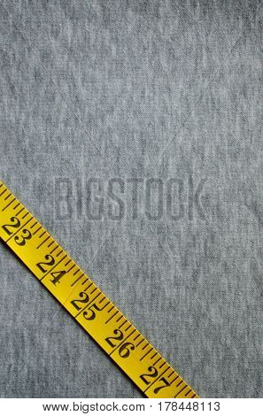 Yellow Measuring Tape Lies On A Gray Knitted Fabric