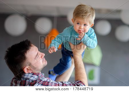 The young father plays with the little son. The kid on hands at the daddy. He ridiculously holds a finger in a mouth.