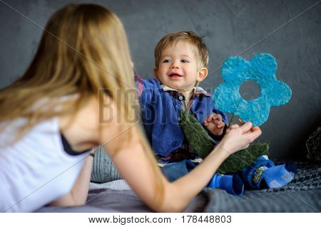 Mother plays with the little son. She shows him a toy. The kid with delight look at mother.