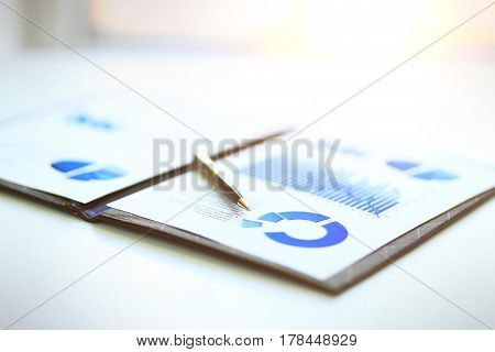 A closeup of a business financial chart with graphs. A pen on top. Represent business expenses, growth or revenue.