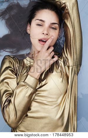 Sensuous woman in golden top in pool