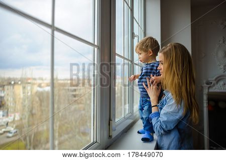 The young woman with the little son are by the big window and look at the street. The kid stands on a window sill mother holds the child.