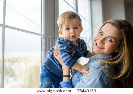 The young woman holds on hands of the little son. She is by the big window. Mother and the son look in the camera.