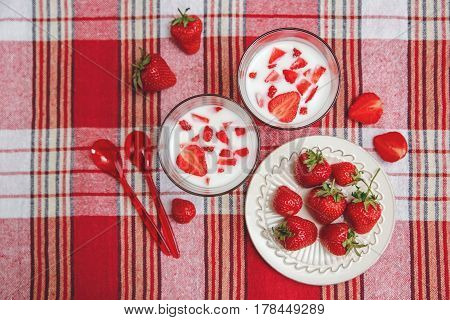 Two Glasses of Yogurt,Red Fresh Strawberries are in the Ceramic Plate with Plastic Spoons on the Check Tablecloth.Breakfast Organic Healthy Tasty Food.Cooking Vitamins Ingredients.Summer Fruits
