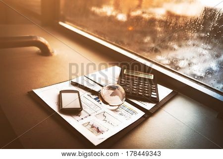 Business financial analysis of the workplace with a globe and phone calculator