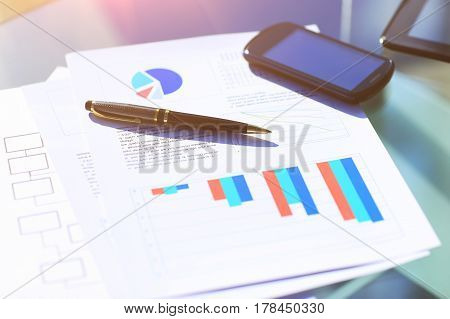 Financial charts on the table with tablet and pen in office