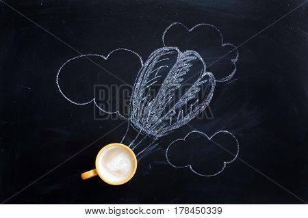 Frothy coffee in a yellow mug against background of balloon drawn in chalk / flying drink