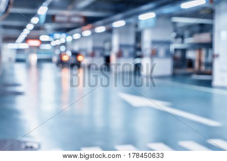 Blurred image/ Parking garage - interior shot of multi-story car park underground parking with cars.