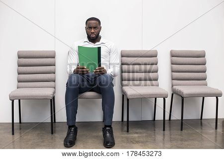 Time for job interview. Young handsome Afro-American man in office. Man sitting, holding his CV, looking at camera and waiting for job interview. Empty chairs are near man. Nice light interior