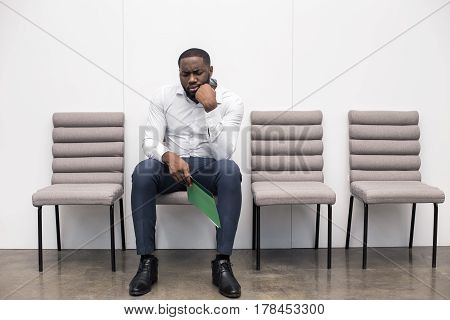 Time for job interview. Young handsome Afro-American man in office. Unhappy man sitting, holding his CV and waiting for job interview. Empty chairs are near man. Nice light interior
