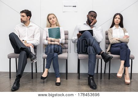 Time for job interview. Young bored men and women in office. They sitting, holding CVs and waiting for job interview. Nice light interior
