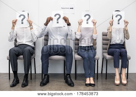 Time for job interview. Young men and women in office. They sitting, holding papers with question sign in front of faces and waiting for job interview. Nice light interior