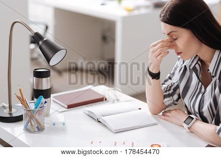 Be thoughtful. Side view photo of excited female touching her nose holding arms on the table while keeping eyes closed