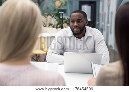 Time for job interview. Young Afro-American man in office while job interview. Women holding CVs and answer the questions. Man looking at candidate and smiling. Nice light interior